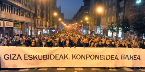 "Marchers carry a sign pronouncing ""Human rights. Solution. Peace. In Bilbao in January 2014."